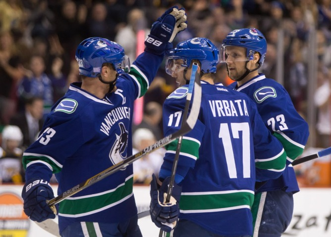 Vancouver Canucks' Henrik Sedin, of Sweden, from left to right, Radim Vrbata, of the Czech Republic, and Alexander Edler, of Sweden, celebrate Edler's goal against the Nashville Predators during the first period of an NHL hockey game in Vancouver, B.C., on Sunday, November 2, 2014. THE CANADIAN PRESS/Darryl Dyck
